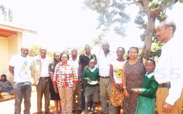 Maureen Atieno (fourth right) with Serian Sacco Chairman, John Sankaire (5th right), Miale ya Tumaini Director, Diana Wamboi and other officials when Serian Sacco donated foodstaffs to Tumaini Children's Home. The Sacco chairman announced that the society will sponsor Atieno's secondary education.
