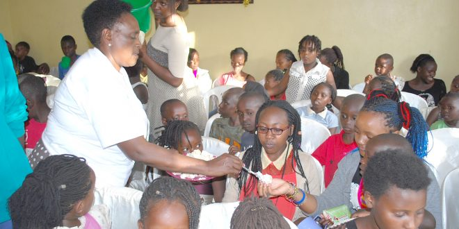 St Paul Children Home director Margaret Mbote shares a cake with children during the 18th  anniversary of the children's home. Photo/Obegi Malack