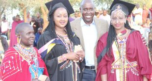 Kajiado County Governor Joseph ole Lenku poses for  a photo with Linet Mapenai and Winfred Mapenai after their graduation thanks-giving party at their Namanga home recently. He urged leaders to support girl-child education. Photo/ Philip Tianda