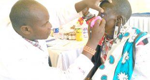 A medic at Kisaju Isinya, checks Mary Nailetoi's eye sight after undergoing a breast and cancer screening during a free medical camp. Photo/Christine Tarayie Musa